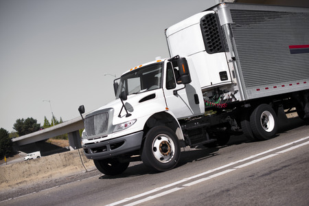 White middle-class semi truck with refrigeration unit on shiny ribbed metal trailer with wires connecting power on the multilane highway road with a concrete median barrier security against the gray raining ready sky. Stock Photo