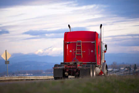 semitruck: Big rig powerful red semi-truck without a trailer with a ladder on the back wall of the cab on the scenic drive along the Columbia River in the background of snowy mountains and cloudy sky