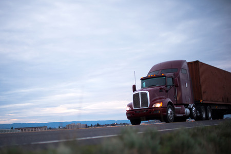 Maroon classic big rig semi truck with headlights transports container on the road running along the industrial and commercial buildings in the evening Archivio Fotografico