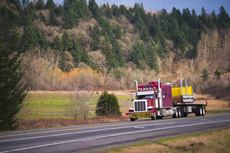 Classic American red semi truck with a big grille and tall tailpipes  and a long cab and an sign over size load transports along a scenic road load large size on a flat bed trailer, amid leafless trees and trees growing on the slopes of the hills Stock Photo
