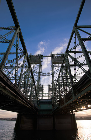 counterweight: Bridge over the Columbia River which forms the federal highway Interstate I-5, connecting Washington and Oregon, the silhouette of the bridge truss construction hoist towers and heavy concrete counterweight to them. Elegant industrial symmetry.