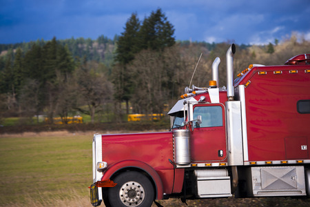 Classic American red big rig semi truck with stainless steel high exhaust pipes visor footrest boxes for equipment on the background of bare trees and trees growing on the slopes of the hills