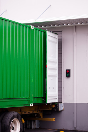 A large metal container green outside with white open door on a semi truck trailer in yellow in a stationary dock warehouse with a metal canopy for loading and unloading cargo. Stock Photo