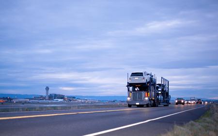 夜の道先護送車のヘッドライトは空港に渡すとのいくつかのレベルで車の輸送のためのトレーラーで大きなリグトラック半 写真素材
