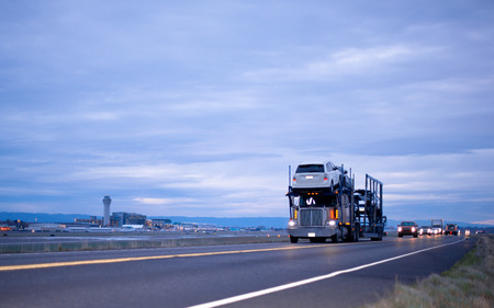 Big rig semi truck with a trailer for transportation vehicles with cars in several levels on evening road ahead convoy of car with headlights passing along Airport Archivio Fotografico