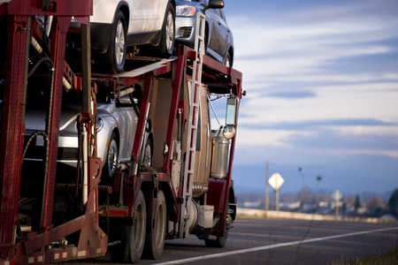 Big truck with dark red trailer for transportation vehicles with cars in tiers on the road against the background of the cloudy sky. Side view. Stockfoto