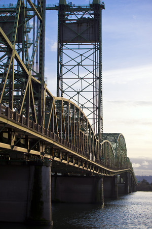 counterbalance: Long automotive and pedestrian drawbridge on concrete piers with arched riveted metal sections and towers Counterbalance uhobit into perspective resting on the opposite shore, with a fragment of the Columbia River.