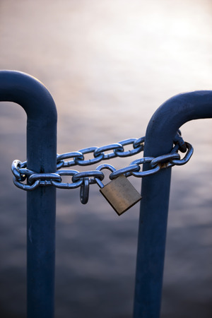 tourniquet: Heavy-duty brass padlock on a large closed circuit swirling around several turnstiles from pipes to limit access of people and vehicles on a certain area of the territory for safety reason. Stock Photo