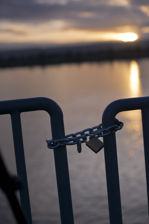 Metal chain with a closed padlock on the turnstile enclosing access to the pier on the river at sunset with reflection path on the water
