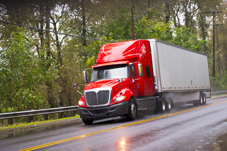 truck road: Big red semi truck shiny and wet from the rain with the reflection of light with a long distance measuring trailer with dust rain under the wheels and reflection of headlights on a wet road passing by green trees. Stock Photo