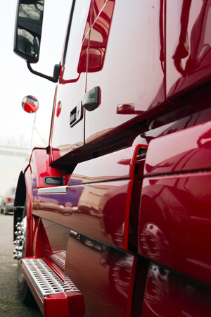 proffessional: Side huge professional red semi truck with glare and light with aluminum elements and exterior automotive parts reflection on the smooth surface of the reflex of the big rig in the parking lot. Stock Photo