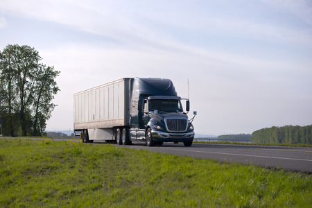 Gorgeous modern shiny dark big rig model semi truck whith headlight transporting cargo at dry van trailer with an aerodynamic spoiler for fuel economy on a scenic road with trees on the horizon.