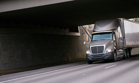 Modern semi truck big rig coffee color with high cabin and trailer with aerodynamic skirt to save fuel and reduce emissions into the atmosphere going on the road under dark concrete bridge with wall.