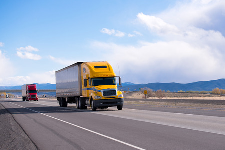 Modern red and yellow big rig semi trucks with trailers come in a convoy, one by one and transported goods straight as an arrow highway with separated lanes on a background of mountains and cloudy sky.