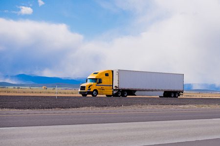 Classic modern semi truck bright yellow color with a white full length trailer aerodynamic skirts on a flat highway in Utah with the blue mountains on the horizon. Modern tool in the trucking industry.