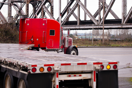 restrictive: Classic big powerful red semi truck with the hood on a bend in the road with a flat bed trailer with red lables restrictive security against a background of old metal bridge truss.