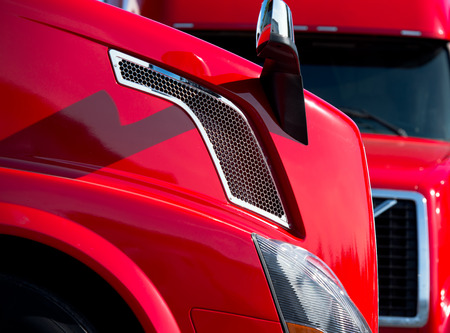 proffessional: Fragments cabins modern red semi trucks, grille, mirrors, lights, fenders, hood in light of daylight. View from close-up Stock Photo