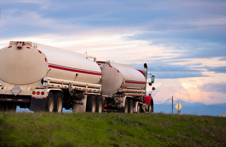 liquids: Stylish classic red semi truck with a large white cylindrical tanks for transportation of fuels and lubricants and other liquids on the scenic road with an evening sunset cloudy sky.