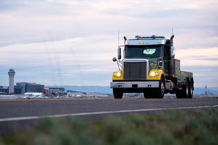The classic modern stylish big rig semi truck with yellow wings and chrome visor and tool box for mobile repair of trucks with big grille on the evening road along the Portland airport control tower.