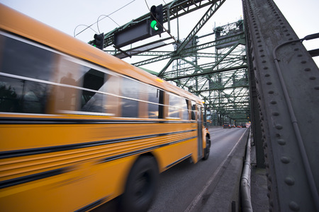Long blurred in motion yellow school bus moves on the metal truss bridge with a green traffic light Zdjęcie Seryjne