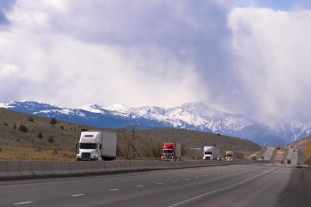 personas en la calle: Camiones semi modernos camiones grandes de diversas marcas y modificaciones con remolque en el convoy van uno a uno y se transportan carga en la carretera con carriles separados a lo largo del terreno monta�oso en el fondo de la sierra nevada y nublado
