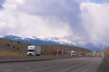 Modern semi trucks big rigs of various brands and modifications with trailers in the convoy go one by one and transported cargo on the highway with separated lanes running along the mountainous terrain on the background of snowy mountain range and cloudy  Stockfoto