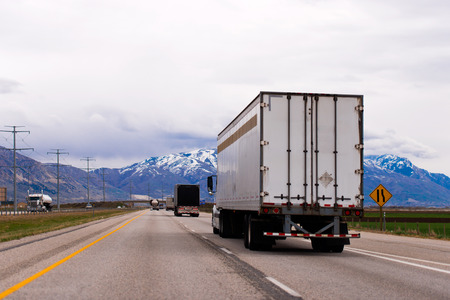 Picturesque straight multilane highway with a dividing strip oncoming traffic flows with a semi trucks and trailers and snow-capped mountains of Utah in the clouds on the horizon, which rests on the interstate road.