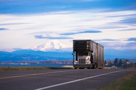 큰 키가 큰 검은 세련된 고전적인 흰색 트럭이 산 봉우리와 눈이 경치에 고급 스러움과 이국적인 자동차의 운송 트레일러에 덮여있다.