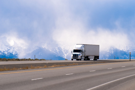 Big white semi truck with a trailer carrying perishable products refrigerator on a straight highway with separated lanes on the background of snowy mountains drowning in the clouds.