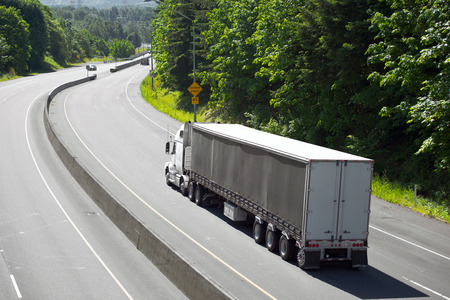 White classic modern semi truck with a long trailer with three powerful bridges and high load capacity at the turn of the highway with a wide concrete separation barrier in the background of green trees.