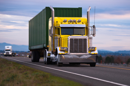 Classic American powerful yellow big rig semi truck with high chrome tailpipes powerful headlights and green container local cargo driving on night road against cloudy sky