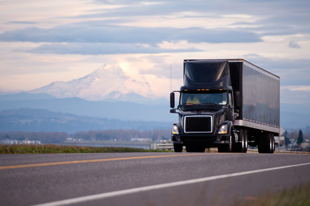 Stylish black modern powerful semi truck and trailer with a black roof spoiler cockpit makes freight on shipping along the scenic road overlooking the beautiful landscape with snowy mountain and cloudy sky