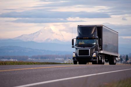 ciężarówka: Stylowe czarne nowoczesne potężnym pół ciężarówki i przyczepy z czarnym spojler dachowy kabiny sprawia ładunków na wysyłce po drodze malownicze widokiem na piękny krajobraz z góry i pochmurne niebo