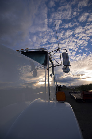 A fragment of a large white semi truck with windshield and mirrors on the background of a spectacular cloud corrugated sky reflected on a shiny plane acrylic painted cabin truck