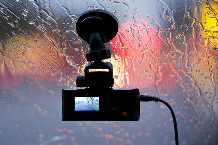 Streaming compact camera for video shooting situations on the road in real-time for safety and report the driver of the car in case of an accident is located on the windshield with rain and a reflection of headlights.