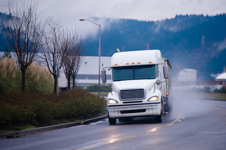 Big white semi truck with a trailer carrying goods covered Tharp at the turn of the road in a cloud of dust storm with reflection of lights included headlights on a wet road with markings and flowerbeds with trees on the roadside in the industrial area.