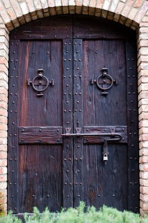 Ancient castle door, dark stained wood with rivets and forged round rings handles and powerful deadbolt closed with a modern lock in the arched wall of the old building, built of brick.