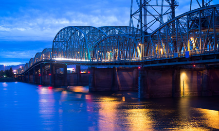 interstate: Arched lifting long sectional bridge on wide concrete piers over the Columbia River which forms the backbone with a moving stream of cars leaving trail of light in the evening with a great reflection of the bright colored lights in the water of the river.