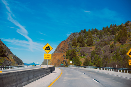 highway signs: Warning road sign ahead of the upcoming downhill for semi truck mounted on a multi highway with a border separating the hills covered with trees, drifting into the horizon. Stock Photo