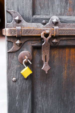 deadbolt: Powerful Forged bolt carved with ornaments and parts for closure on an old wooden door with rust on the deadbolt and modern yellow padlock, as a meeting of old and new eras.