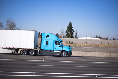 freightliner: Bright blue modern road train of the semi truck and the dry van trailer streamlined aerodynamic skirt on the highway with lots of traffic lanes separated by markings and concrete fence. Side view.