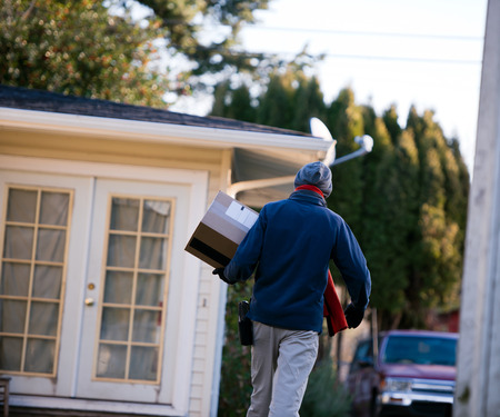 keeping: Man on the delivery of parcels with shipped box and a scanner on the belt goes to the house with a glass door surrounded by trees brought to deliver the goods. Stock Photo
