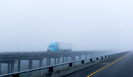 semitruck: Modern big blue rig semi-truck with a trailer with lights on transports cargo on a long concrete viaduct over the ravine on the supports on the highway in foggy weather.