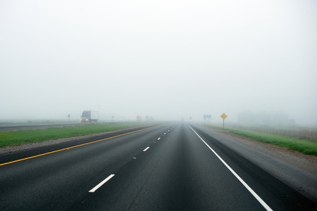 convoy: The convoy of semi trucks of various models and brands on the milk fog-drenched straight interstate highway line separated oncoming traffic going into the horizon hidden veil of mist.