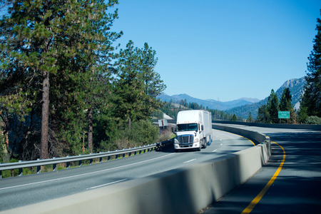 scenic highway: Fast and powerful heavy-lift modern white semi truck with a full size trailer at the turn of mountain scenic highway passing through the pass surrounded by evergreen spruce and mountain ranges in North America.