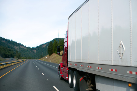 Large modern red semi truck with trailer rushed to a point on the horizon, which converges multi-lane highway on which rides a truck, line markings and roadside covered with green trees