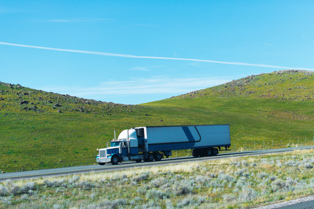 refrigeration: Classic powerful semi truck with high chrome tailpipes and a trailer with a refrigeration unit for transport of temperature-sensitive food on the road to California hills covered with grass.