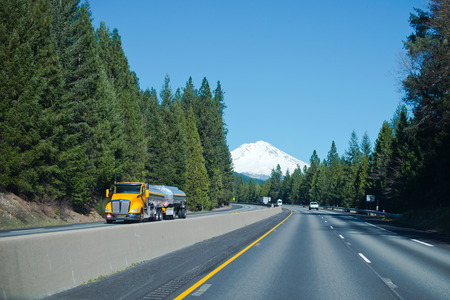semitruck: Modern bright yellow semi-truck with two shiny stainless steel tanks on the main multilane highway with the separation concrete curbs in the beautiful environment evergreen trees and snowy verschiny high mountains on the horizon.
