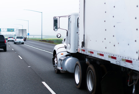 semitruck: Professional white classic semi-truck with white trailer to haul industrial cargo transports cargo on the highway with other road users in foggy weather on the plateau in California. Stock Photo