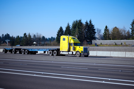 A super-heavy yellow semi tractor classic style with chrome accessories and parts with a powerful multi-axle flat bed trailer to transport bulky cargo on a wide multi-lane highway in the light of sunlight.